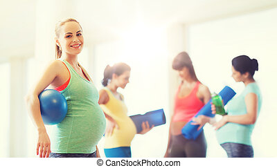 happy pregnant woman with ball in gym
