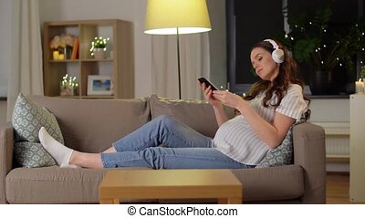 pregnant woman with smartphone and headphones - pregnancy, ...