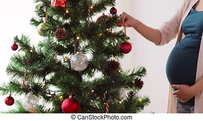 pregnant woman decorating christmas tree at home -...