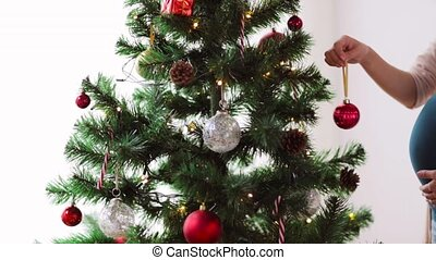 pregnant woman decorating christmas tree at home