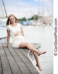 pregnancy woman sitting at sea port