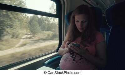 Pregnancy Woman Working with Smartphone on a Train