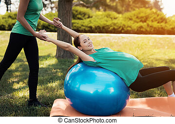 Pregnancy yoga. A woman is doing exercises on a blue ball for yoga. The coach helps her