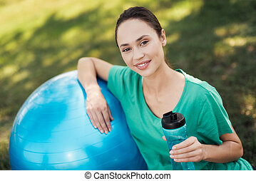 Pregnancy yoga. Pregnant woman in a green T-shirt is sitting by the blue ball for yoga
