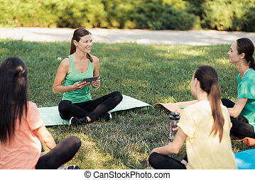 Pregnancy yoga. The trainer sits in front of a group of pregnant women and looks at something on his tablet