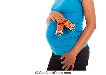 pregnant african holding baby shoes