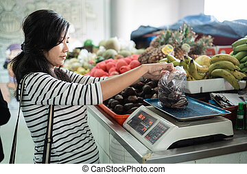 pregnant asian woman weigh the items purchased