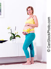 Pregnant blonde woman in her home.