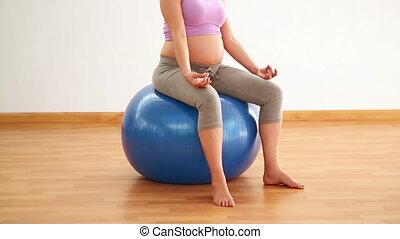Pregnant brunette meditating on exercise ball in a fitness...