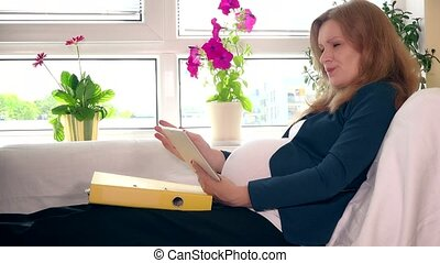 Pregnant business woman with tablet computer and binder files working at home
