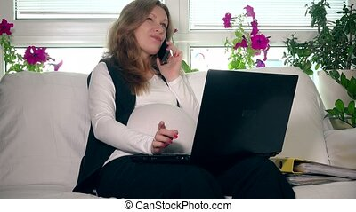 Pregnant business woman woman talking phone and working with computer at home