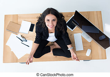 pregnant businesswoman on table in lotus pose