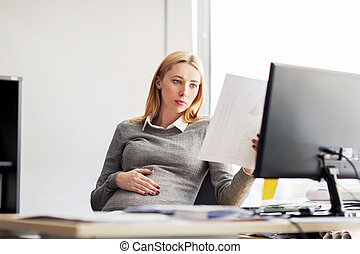 pregnant businesswoman reading papers at office - pregnancy,...
