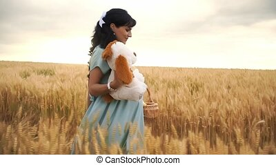 Pregnant caucasian lady walks in a meadow and is going to have a picnic on nature in slowmo