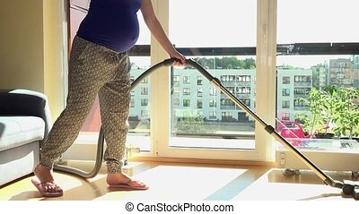 Pregnant caucasian woman cleaning wooden floor with vacuum cleaner at home