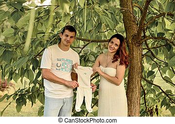 pregnant couple holding children's pajamas outdoor