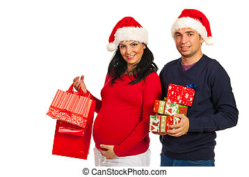 Pregnant couple holding Christmas gifts