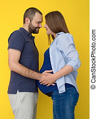 pregnant couple isolated over yellow background