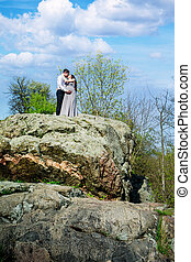 Pregnant couple on a rock