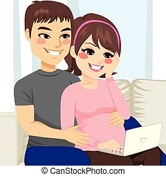 Pregnant Couple Sofa Laptop - Young pregnant couple sitting...