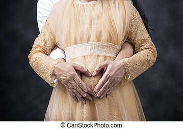 Pregnant couple touching belly and showing heart symbol with hand