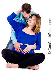 Pregnant couple with a heart shape - A young couple ...