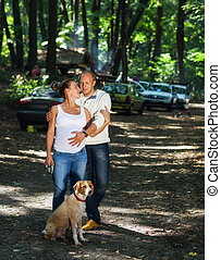 Pregnant couple with puppy in a forest