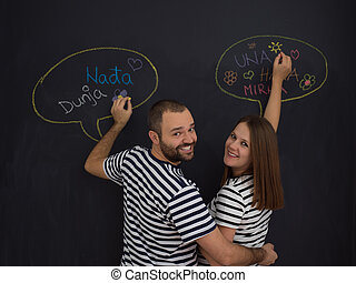pregnant couple writing on a black chalkboard