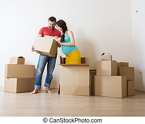 Pregnant couple - Young couple is moving into new house with...