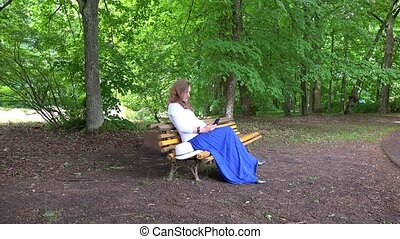 Pregnant female browse with smartphone sitting on park bench
