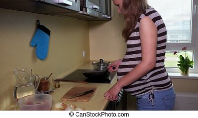 Pregnant female cook food in kitchen cooking pan on hob....