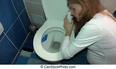 pregnant female girl vomiting in toilet bowl in bathroom. Sad woman morning sickness. Handheld steadycam flycam movement shot.