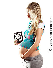 Pregnant woman with clocks, waiting for new life