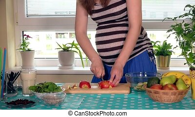 Pregnant female stomach and hands slicing apple fruit on cutting board