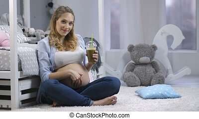 Pregnant female with green smoothie smiling - Gorgeous young...