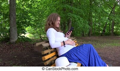 Pregnant female with smartphone sitting on park bench