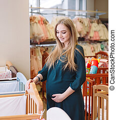 Pregnant girl chooses a baby cot in the store. - Pregnant ...