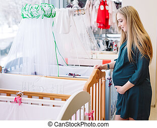 Pregnant girl chooses a baby cot in the store.