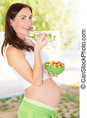 Pregnant girl having breakfast