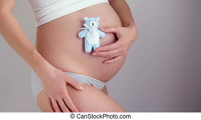 pregnant girl holding little bear toy blue color from your...