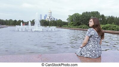 Pregnant girl in the background of a fountain - Against the...