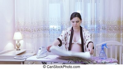 Pregnant girl ironing clothes - On an ironing board the...