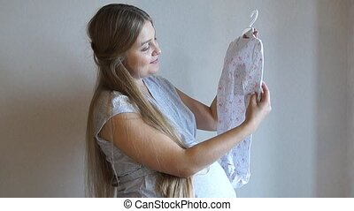 Pregnant girl. Pregnant woman holds a newborn clothes in her hands. Baby clothes