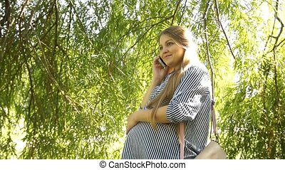 Pregnant girl. Pregnant woman in park. Woman talking at phone