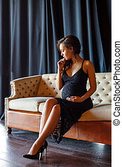 pregnant girl sitting on the couch in a beautiful dress