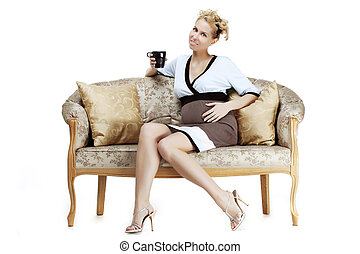 Pregnant girl sitting on the sofa with a cup