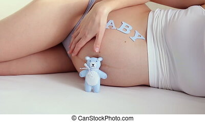pregnant girl stroking her belly in bed