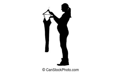 Pregnant girl tries on things. Silhouette. White background....