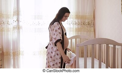 Pregnant girl veiled baby bed - Near the child's bed a...