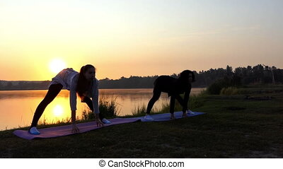 Pregnant Girl With Her Trainer Practice Yoga on the Lake at Sunset in Slo-Mo